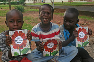 Three boys show off the BFA books they were given as a reward for helping set up a community library in The Gambia.
