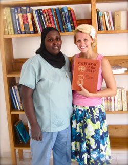 Fatu, the head dental nurse, and Megan Meyer, director of A Hand in Health, show off dental books collected from the University of Minnesota School of Dentistry.