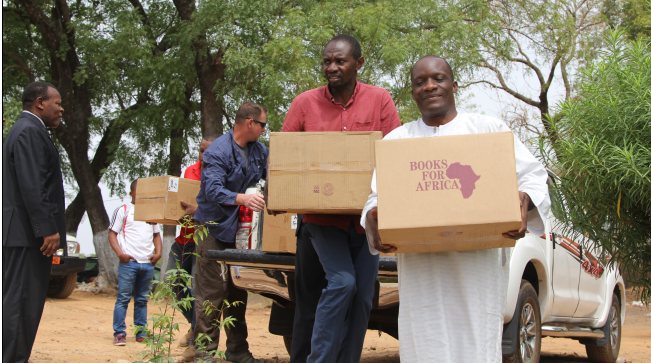 Garoua Linguistic Center staff and students work with CAT 4032 to unload donated books